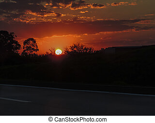 A beautiful view of a reddish sunset with a dark road in the foreground