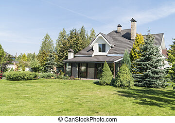 village house with its beautiful garden in a rural area under blue sky