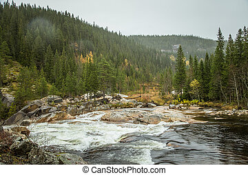 A beautiful waterfall in a central Norway. Colorful autumn landscape at the river.