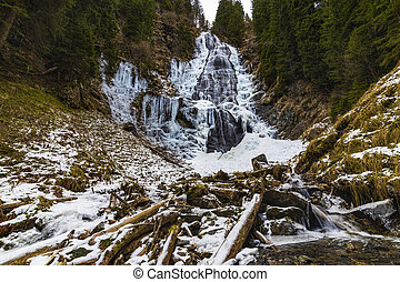 A beautiful waterfall in the mountains during winter day,