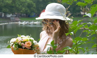 A beautiful white girl in a white hat, with a bouquet of flowers.