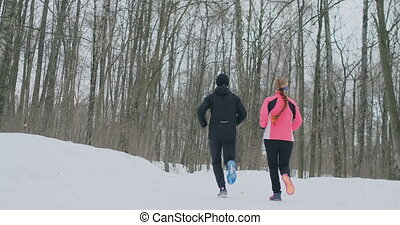A beautiful woman and a man are running in the forest in winter proper nutrition and a healthy lifestyle. Slow motion.