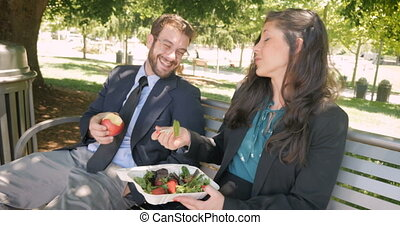 A beautiful woman and man eating healthy food and flirting with each other