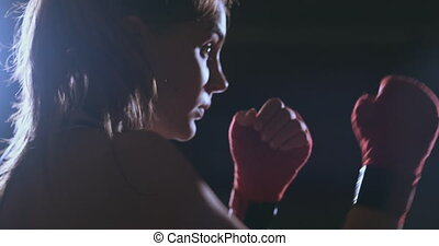 A beautiful woman boxer trains in a dark gym and works out...