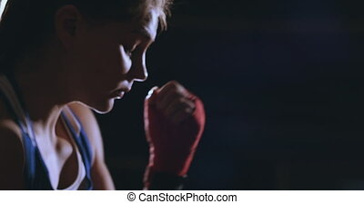 A beautiful woman boxer trains in a dark gym and works out punches in slow motion. side view. Steadicam shot