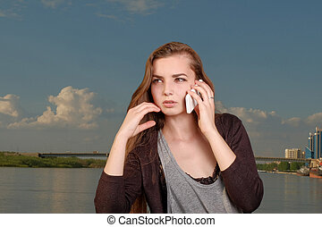 A beautiful woman chatting via phone and looking away against big blue sky and river.