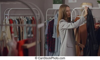 A beautiful woman chooses clothes in a branded clothing showroom.