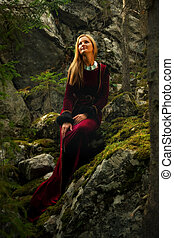 A beautiful woman fairy with long blonde hair in a historical gown is sitting amids moos covered rocks in enchanting forestral landscape