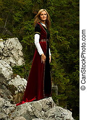 A beautiful woman fairy with long blonde hair in a historical gown is standing on rocks amids a breathtaking forestral landscape
