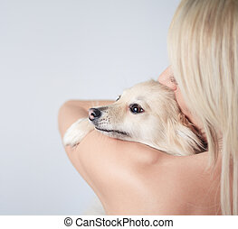 A Beautiful woman fashion, holding dog in studio gray background