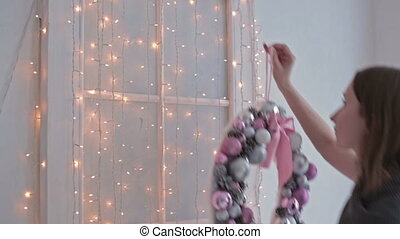 A beautiful woman hanging a Christmas wreath on her home