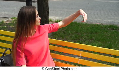 woman in a red suit makes selfie in Park