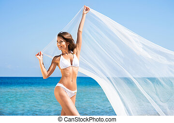 A beautiful woman in a swimsuit posing with a silk blanket on the beach