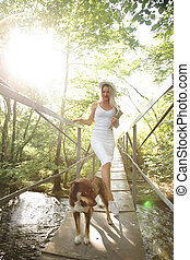 A beautiful woman in a white dress and white hat goes over the black river on the bridge with dog.