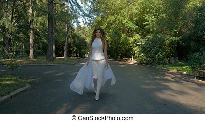 A beautiful woman in a white suit is walking along the path in the park.