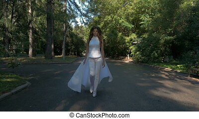A beautiful woman in a white suit walks quickly and runs in the city park.