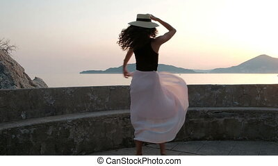 A beautiful woman in high heels and in a light dress is dancing gracefully with a hat on platform