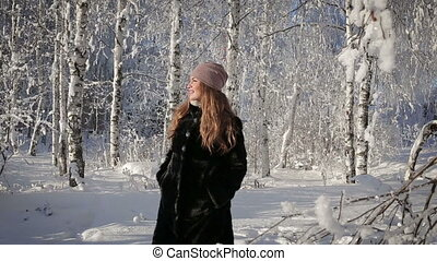 A beautiful woman is happy and walks in the park on a winter day.