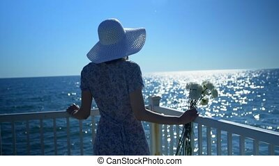 A beautiful woman is standing on the sea wharf and looks at the blue sky and water space.
