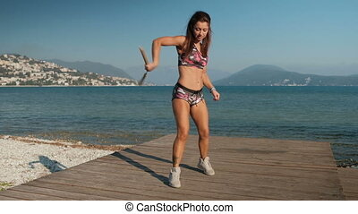 A beautiful woman on a sea pier skillfully turns wooden nunchakas.