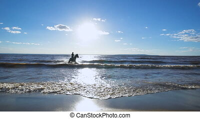 A beautiful woman riding a horse at a lake