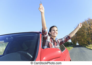 A beautiful woman sitting in her new car, holding the keys.