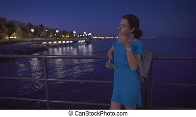 A beautiful woman standing near the sea and looking at night city panorama