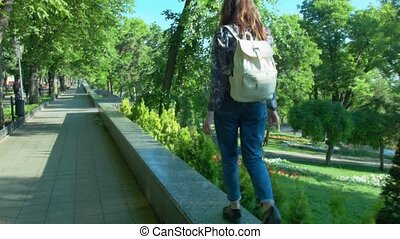 A beautiful woman walks the parapet along the street. She is young with a backpack.