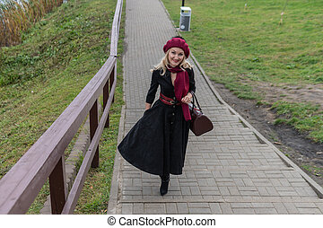 A beautiful woman walks up the stairs and in burgundy pall and biret, an adult with a beautiful smile in black clothes, in the fall against the background of a pond, blue clouds.