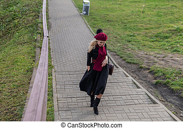 A beautiful woman walks up the stairs, both in burgundy palette and biret, looks at the camera in black clothes, in the fall against the background of the pond there are blue clouds.