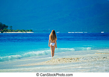 A beautiful woman wearing white bikini facing the sea on a vacant beach in paradise