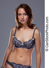 A beautiful woman with a bra and slip on grey background