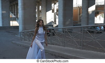 A beautiful woman with long hair goes up the stairs.