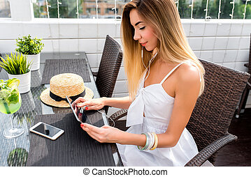 A beautiful woman with long hair is sitting in cafe on summer porch. In hands of tablet, listening to music on headphones, watching a video. A glass of lime cocktail phone straw hat on the table.