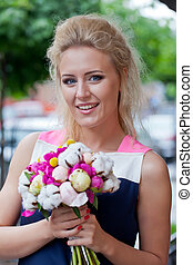a beautiful young blond girl in summer dress with a bunch of flowers is smiling for the camera