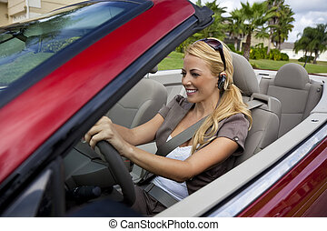A beautiful young blond woman driving her convertible car and talking on her cell phone with a bluetooth headset