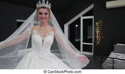 bride with crown on her head makes minute with hands on veil...
