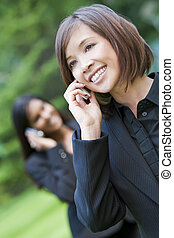 A beautiful young Chinese Asian oriental woman with a wonderful smile chatting on her cell phone, behind her is an Indian Asian colleague on her cell phone.