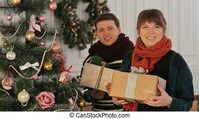A beautiful young couple in love near the New Year tree giving presents to the viewer. Christmas and New Year themes.