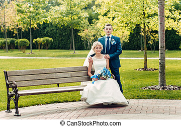 beautiful young fair-haired bride sits on a bench next to the groom in an exotic park