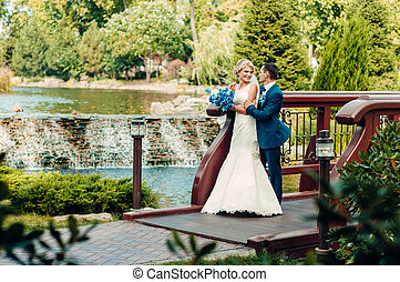 beautiful young fair-haired bride stands next to the groom in an exotic park