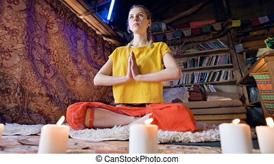 A beautiful young girl in loose clothes sits in a craft room...