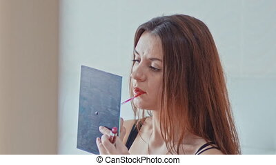 A beautiful young girl paints her lips,sitting on the bed in the bedroom