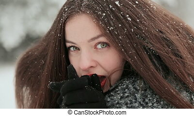 A beautiful young girl with chic long hair is enjoying falling snow in winter. Face close-up.