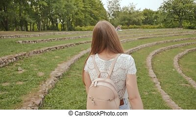 A beautiful young girl with long hair and a backpack on her back is walking happily along the green stadium, enjoying nature and relaxing in the summer.