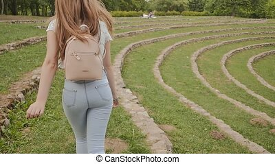 A beautiful young girl with long hair and a backpack on her back running along a green stadium, enjoying nature and relaxing in the summer.