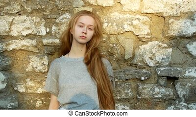 A beautiful young girl with long hair stands near a stone wall and looks at the camera