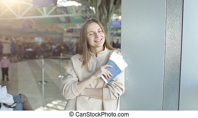 A beautiful young lady is happy that she is traveling to another country. cheerful woman getting visa, holding tickets passport for airplane flight trip, summer vacation concept.