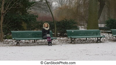 A beautiful young lady sits still on a bench slow motion