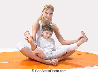 A beautiful young mother practices yoga with her son